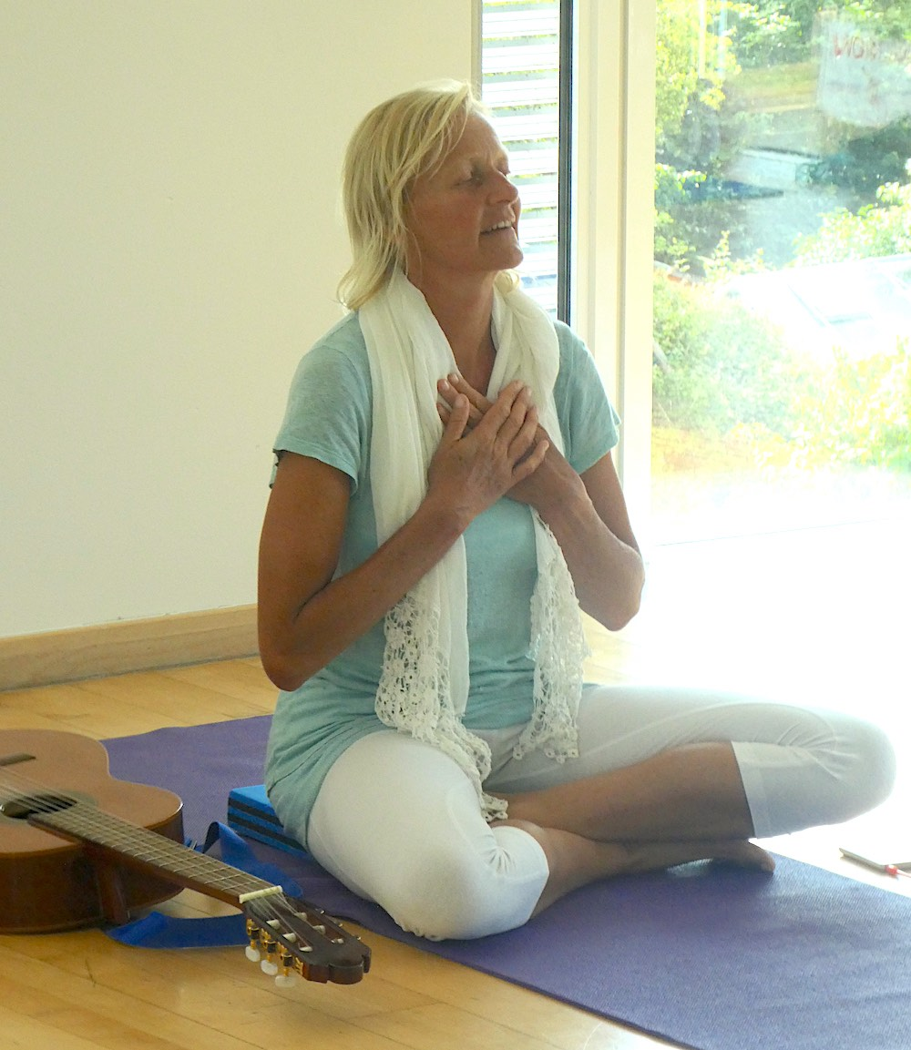 Woman in serene yoga pose with a guitar beside her.