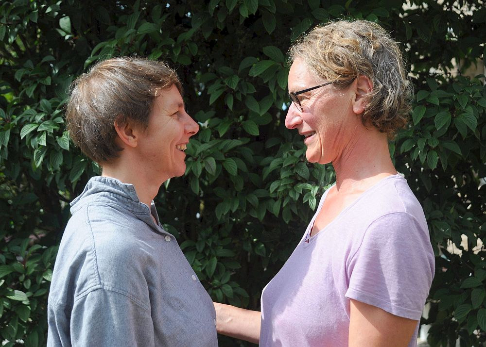 Two women standing face to face smiling at each other